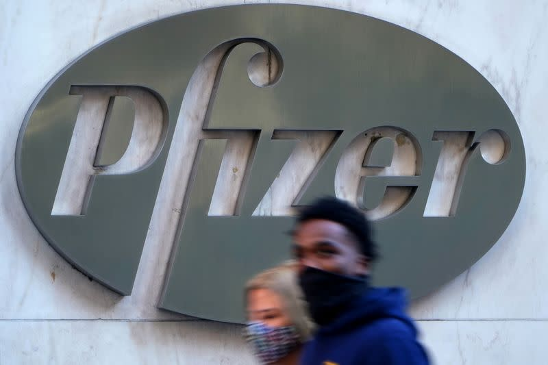 People walk past the Pfizer Headquarters building