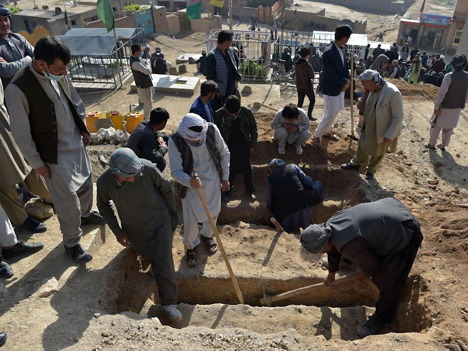Shiite mourners and relatives dig graves for schoolgirls who died in multiple blasts outside a school in Kabul (AFP via Getty Images)