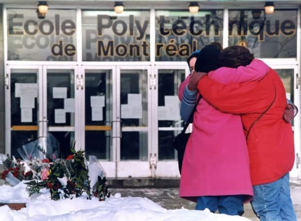 Three unidentified women hug each other after laying flowers in front of the Polytechnical School at the University of Montreal on Dec. 9, 1989.