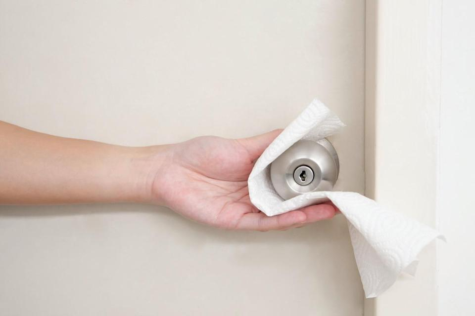 hand opening the public doorknob with tissue paper