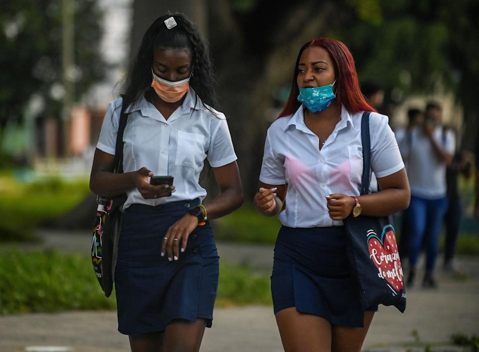 Youths wearing face masks walk to the Pedagogic School Fulgencio Oroz Gomez in Havana on October 4, 2021, nine months after it was closed due to the novel coronavirus pandemic. - Students of 12th grade, third and fourth year of Pedagogic and third year of the Technical Professional Education are making a gradual return to classrooms marked by the progress of the vaccination against COVID-19. (Photo by Yamil LAGE / AFP) (Photo by YAMIL LAGE/AFP via Getty Images)