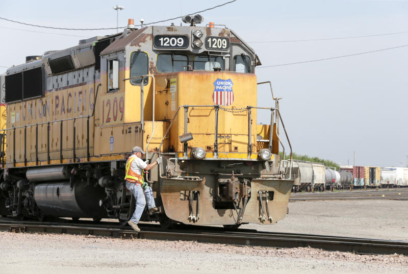 A Union Pacific employee climbs on board a locomotive in a rail yard in Council Bluffs, Iowa, Thursday, July 20, 2017. (AP Photo/Nati Harnik)