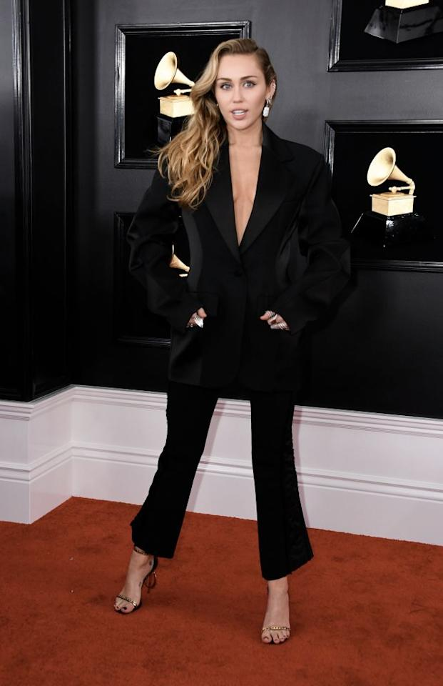 "<p>Did you really think Miley Cyrus would wear a plain old dress? The songstress, who always commands attention, rocked a blazer sans shirt underneath, along with personalized ""MC"" shoes. </p>"