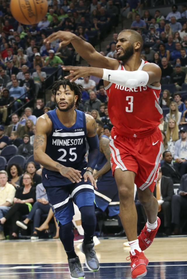 Houston Rockets' Chris Paul, right, makes a pass as Minnesota Timberwolves' Derrick Rose pursues during the second half of Game 4 in an NBA basketball first-round playoff series Monday, April 23, 2018, in Minneapolis. The Rockets won 119-100. (AP Photo/Jim Mone)
