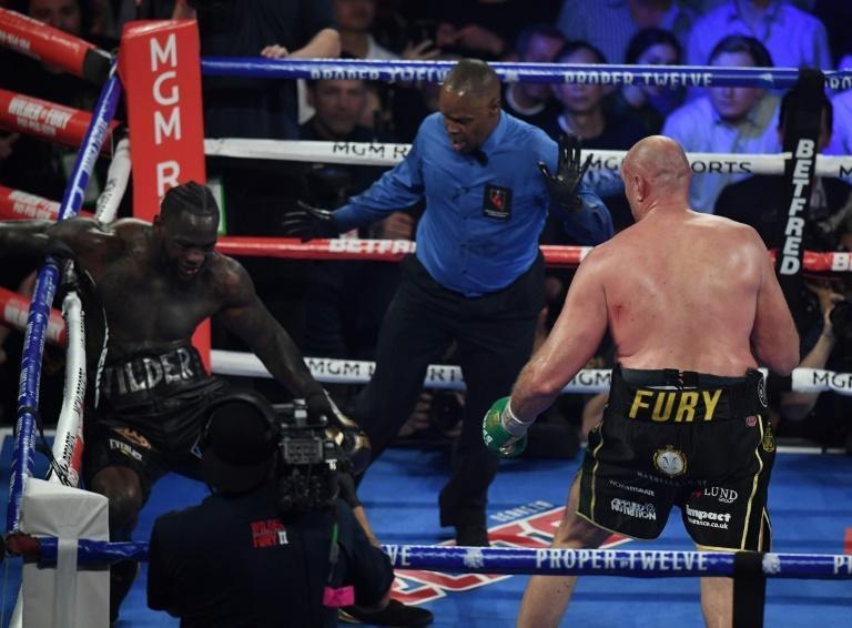 British boxer Tyson Fury, right, knocks American Deontay Wilder down before stopping him in the seventh round during their World Boxing Council heavyweight championship fight in front of a crowd of 15,800 at the MGM Grand Garden Arena in Las Vegas (AFP Photo/Mark RALSTON)