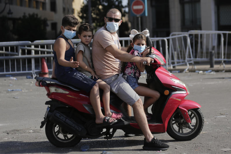 A family riding a scooter check the aftermath of a protest against the Lebanese government in Beirut, Lebanon, Saturday, Oct. 19, 2019. The blaze of protests was unleashed a day earlier when the government announced a slate of new proposed taxes, including a $6 monthly fee for using Whatsapp voice calls. (AP Photo/Hassan Ammar)
