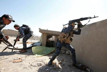 An Iraqi federal policeman fires his rifle at Islamic State fighters' positions at Bab al Jadid district in the old city of Mosul