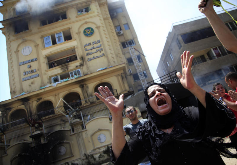An Egyptian woman chants slogans, as protesters ransack the Muslim Brotherhood headquarters in the Muqattam district in Cairo, Monday, July 1, 2013. Protesters stormed and ransacked the headquarters of President Mohammed Morsi's Muslim Brotherhood group early Monday, in an attack that could spark more violence as demonstrators gear up for a second day of mass rallies aimed at forcing the Islamist leader from power. (AP Photo/Khalil Hamra)