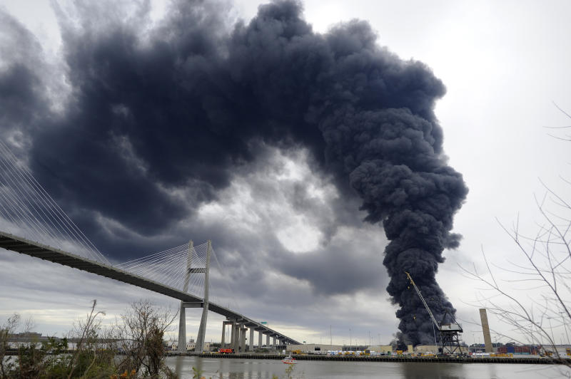 Firefighters battle a blaze in a warehouse at the Georgia Ports Authority Ocean Terminal, Saturday, Feb. 8, 2014, in Savannah, Ga. Burning rubber from the fire at the Port of Savannah sent up a towering column of black smoke that could be seen from miles away. The cause of the fire wasn't immediately known, but all port workers were accounted for and unharmed.(AP Photo/Stephen B. Morton)