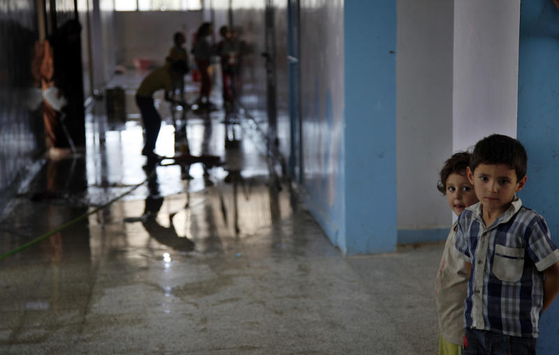 Syrian children clean a school where they fled to from the fighting in town of Kafr Hamra some ten kilometers. (six miles)north of the center of Aleppo city, Syria, Tuesday, Aug. 7, 2012. (AP Photo/ Khalil Hamra)