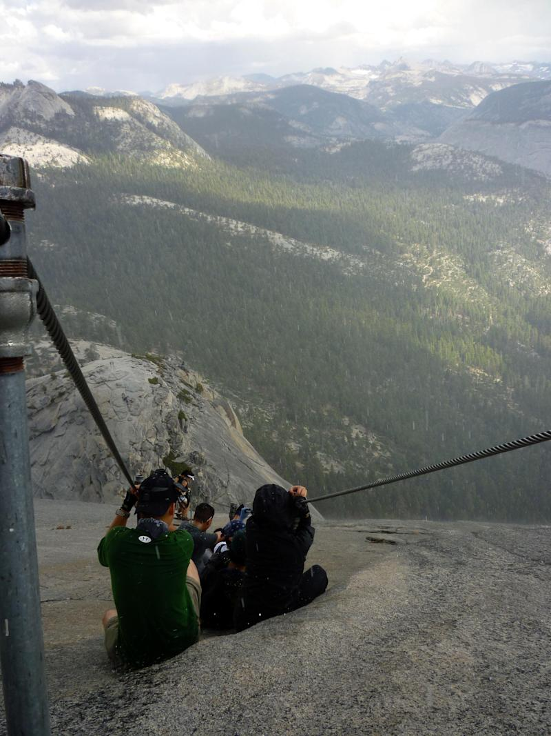 """In this Sept. 24, 2011 photo provided by Armando Castillo, hikers descend Half Dome in Yosemite, National Park. Armando Castillo knew he should not attempt the last treacherous stretch up Half Dome with storm clouds looming. But he felt he had come too far not to accomplish his goal. """"About three quarters of the way up it started hailing,"""" he said. """"There's a bunch of people and everybody just stops. Some women started crying because it was slippery and pretty scary. Then it cleared up.""""  While others turned back, Castillo pushed on, making him one of Yosemite National Park's worst nightmares, an increasing number of wilderness neophytes who mistakenly think the government is obligated to save them. (AP Photo/Armando Castillo)"""