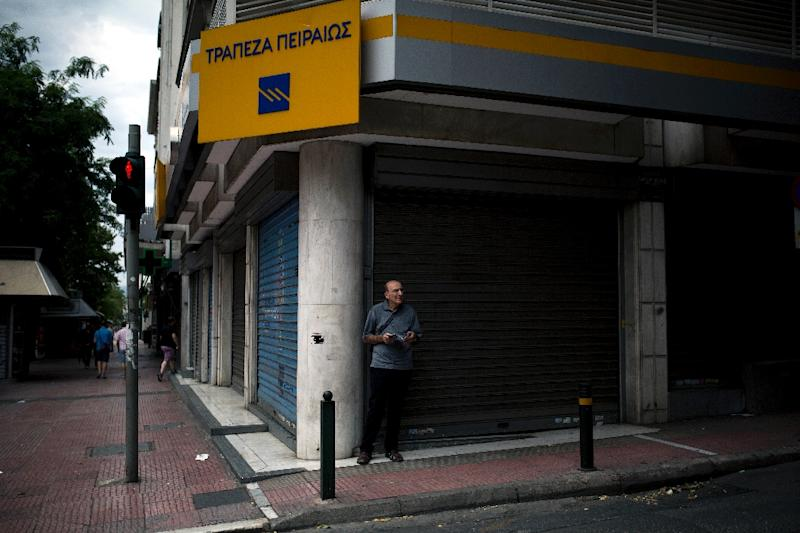 A man stands in front of a branch of the Piraeus bank in Athens on June 27, 2015 (AFP Photo/Angelos Tzortzinis)
