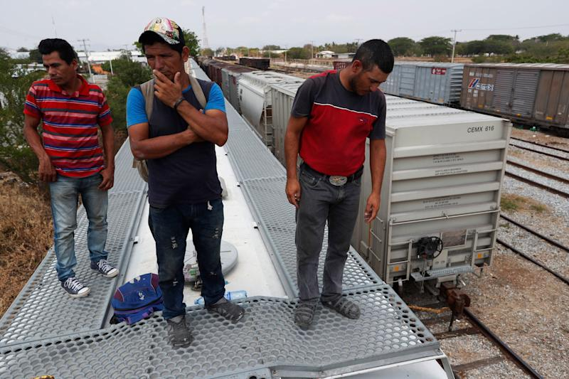 Honduran migrants Jose Francisco Mendez, left, Denis Funes, center, and Jose Mendoza stand on top of a freight train during their journey toward the U.S.-Mexico border, in Ixtepec, Oaxaca State, Mexico, Tuesday, April 23, 2019. Funes says he saw a fellow Honduran knocked off the train the previous night by a low-hanging branch that caught the man in the face and sent him hurtling to the tracks below. (AP Photo/Moises Castillo)
