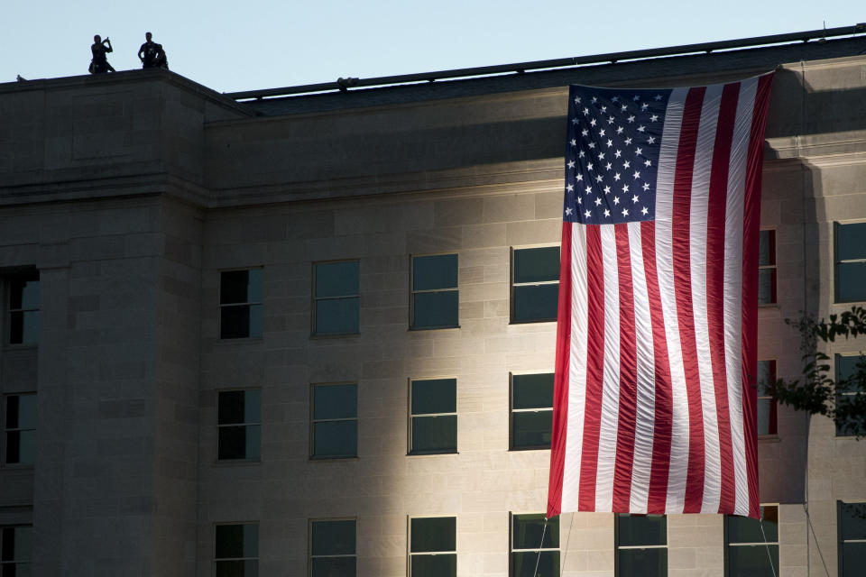 FILE - In this Sept. 11, 2015, file photo an American flag is draped on the side of the Pentagon where the building was attacked Sept. 11, 2001, on the 14th anniversary of the attack. As the 20th anniversary of the Sept. 11, 2001, terrorist attacks approaches, Americans increasingly balk at intrusive government surveillance in the name of national security, and only about a third believe that the wars in Afghanistan and Iraq were worth fighting, according to a new poll by The Associated Press-NORC Center for Public Affairs Research. (AP Photo/Jacquelyn Martin, File)