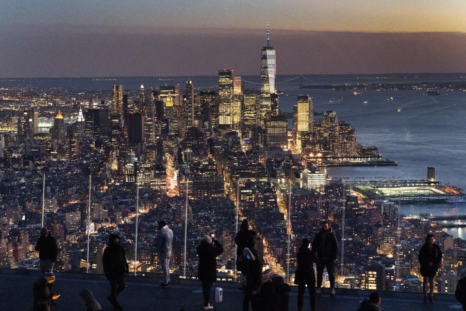FILE - Visitors to the Edge, an outdoor observation deck 1100 feet above the ground, look at the lights of Manhattan, March 2, 2021, in New York. New York will lose one seat in Congress as a result of national population shifts, according to census data released Monday. (AP Photo/Mark Lennihan, File)