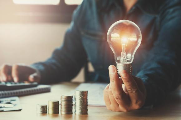 A man holding a light bulb next to a growing stack of coins.