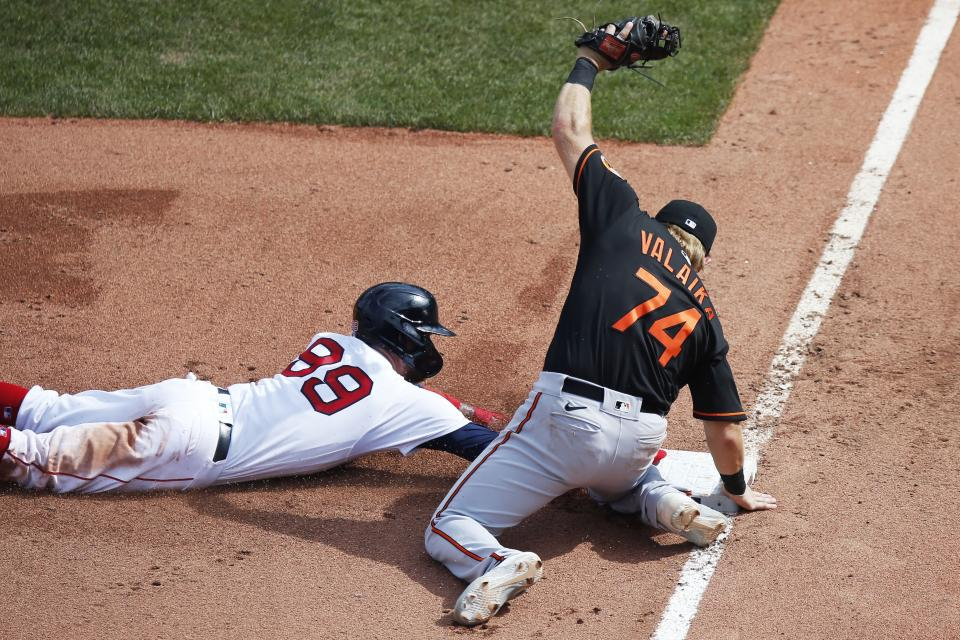 Boston Red Sox's Alex Verdugo (99) is safe at third base after the ball got by Baltimore Orioles' Pat Valaika (74) on a throwing error by Orioles' Anthony Santander during the sixth inning of a baseball game Saturday, July 25, 2020, in Boston. (AP Photo/Michael Dwyer)