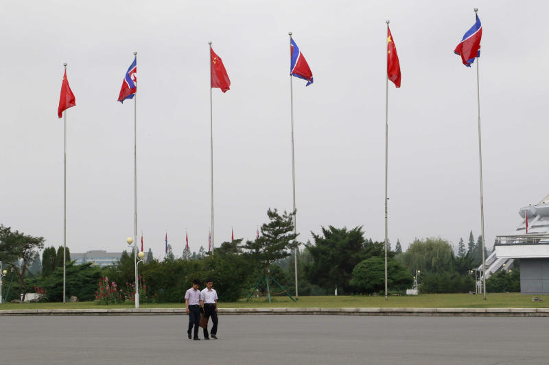 North Korean walk on a street where North Korean and Chinese national flags are hoisted in Pyongyang, North Korea Thursday, June 20, 2019. Chinese President Xi Jinping arrived Thursday morning for a two-day state visit to North Korea, where he is expected to talk with leader Kim Jong Un about the stalled negotiations with Washington over North Korea's nuclear weapons. (AP Photo/Cha Song Ho)