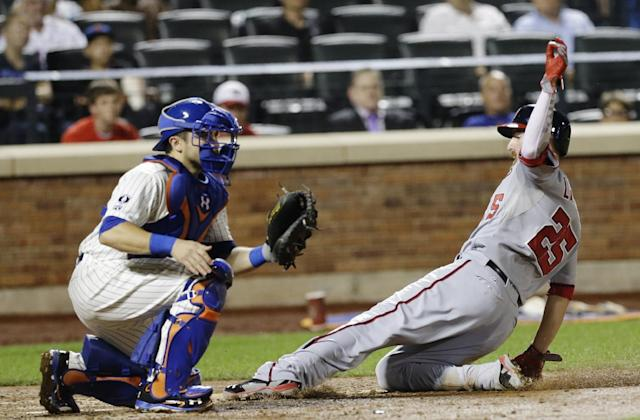 Washington Nationals first baseman Adam LaRoche (25) slides past New York Mets catcher Travis d'Arnaud to score on a sacrifice fly by Bryce Harper during the seventh inning of a baseball game Wednesday, Aug. 13, 2014, in New York. (AP Photo/Frank Franklin II)
