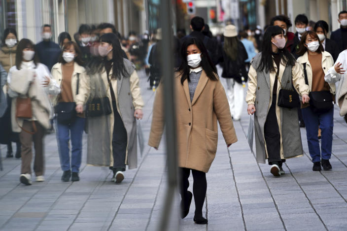 People wearing protective masks to help curb the spread of the coronavirus walk on a street Monday, March 1, 2021, in Tokyo. The Japanese capital confirmed more than 120 new coronavirus cases on Monday. (AP Photo/Eugene Hoshiko)