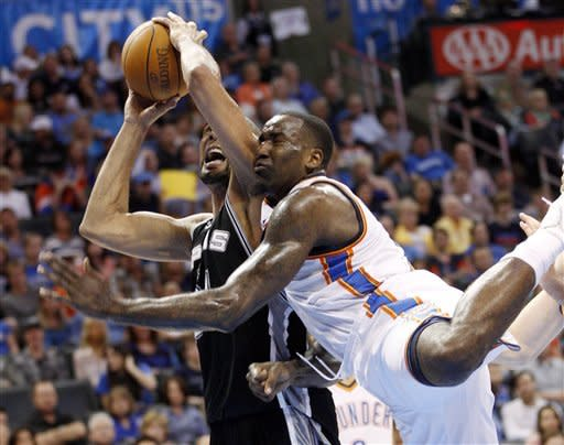 Oklahoma City Thunder center Kendrick Perkins, right, fouls San Antonio Spurs forward Tim Duncan, left, as he shoots in the first quarter of an NBA basketball game in Oklahoma City, Friday, March 16, 2012. (AP Photo/Sue Ogrocki)