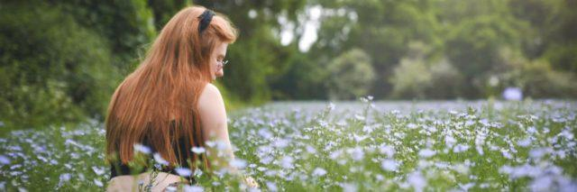 photo of woman sitting in field with white flowers