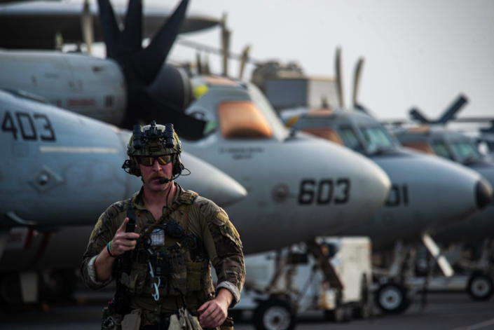 In this photo provided by the U.S. Navy, Explosive Ordnance Disposal Technician 3rd Class Ethan Tews walks across the flight deck of aircraft carrier USS Ronald Reagan to board an MH-60S SeaHawk helicopter to head to an oil tanker that was attacked off the coast of Oman in the Arabian Sea on Friday, July 30, 2021. An attack on an oil tanker linked to an Israeli billionaire killed two crew members off Oman in the Arabian Sea, authorities said Friday, marking the first fatalities after years of assaults targeting shipping in the region. (Mass Communication Specialist 2nd Class Quinton A. Lee/U.S. Navy, via AP)