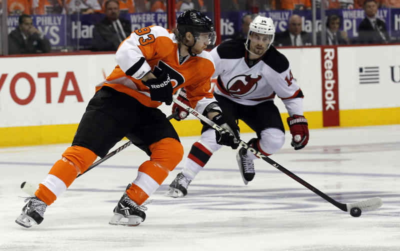 Philadelphia Flyers right wing Jakub Voracek (93), from the Czech Republic, skates with the puck as he is defended by New Jersey Devils center Adam Henrique (14) in the first period of Game 1 in a second-round NHL Stanley Cup hockey playoff series, Sunday, April 29, 2012, in Philadelphia. (AP Photo/Alex Brandon)