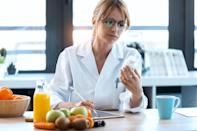 Shot of woman nutritionist doctor writes the medical prescription for a correct diet on a desk with fruits, pills and supplements.