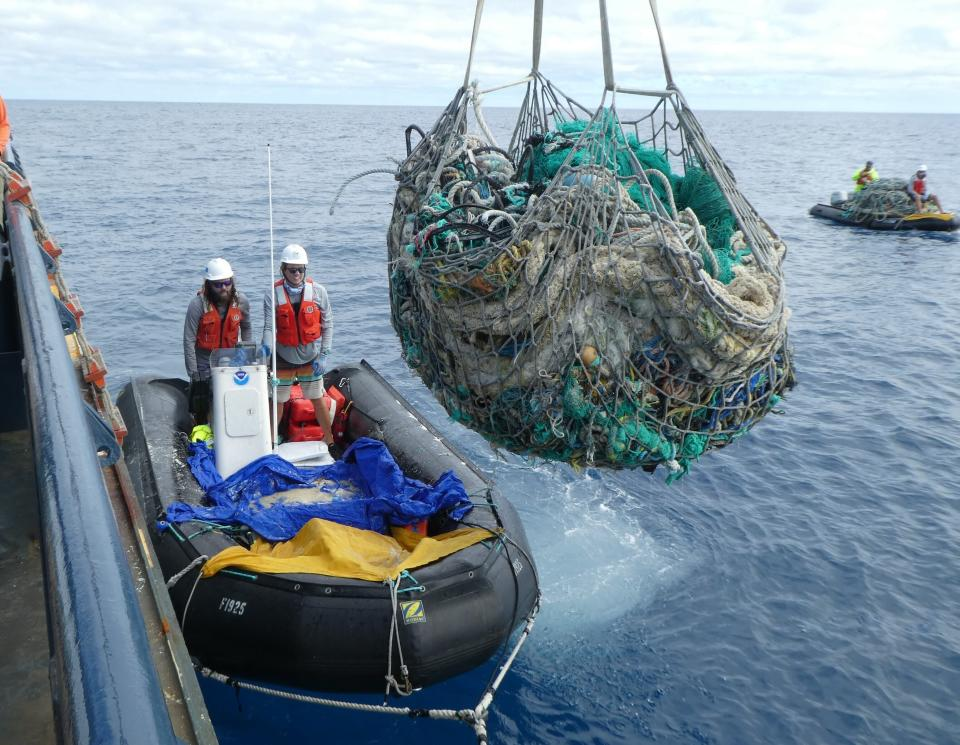In this April 11, 2021 photo provided by Matt Saunter, Joao Garriques, left, and Matthew Chauvin load fishing nets onto a ship near Kure Atoll in the Northwestern Hawaiian Islands. A crew has returned from the remote Northwestern Hawaiian Islands with a boatload of marine plastic and abandoned fishing nets that threaten to entangle endangered Hawaiian monk seals and other marine animals on the tiny, uninhabited beaches stretching for more than 1,300 miles north of Honolulu. (Matt Saunter, Papahanaumokuakea Marine Debris Project via AP)