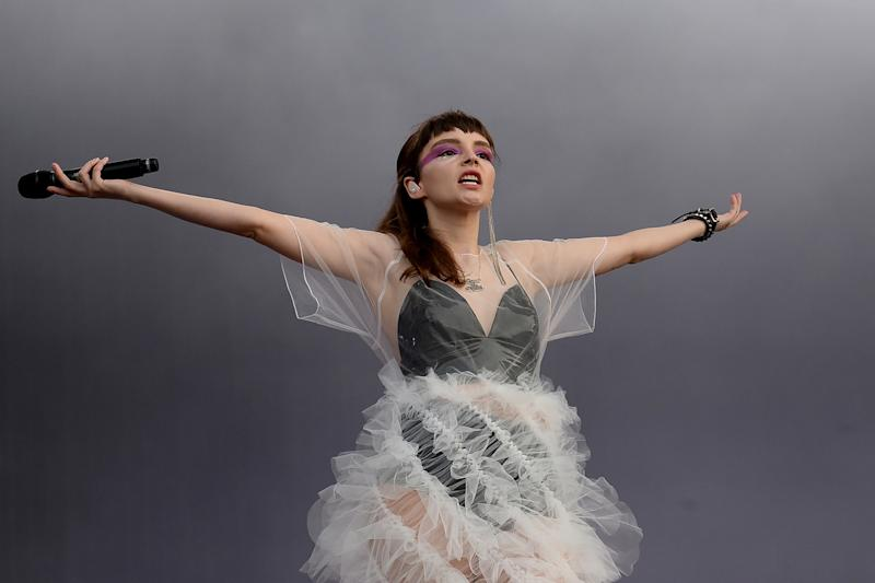 "At the Latitude Festival, Lauren Mayberry wears Roberts-Wood's white non-stitched Vortex dress made, writes the designer, ""using pattern cutting to engineer a single pattern piece that twists and rotates as it is assembled to form the whirling design."""