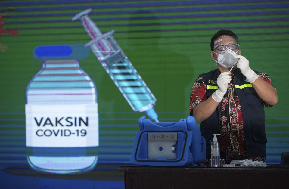 A health worker prepares to give the COVID-19 vaccine to a government official in Medan, North Sumatra, Indonesia, Thursday, Jan. 14, 2021. Indonesia started vaccinating health workers and public servants against COVID-19 on Thursday, a day after President Joko Widodo received the first shot of China's Sinovac Biotech vaccine. The Health Ministry is planning to vaccinate more than 1.3 millions health workers and 17.4 millions public officers in the first stage in the world's fourth most populated country. (AP Photo/Binsar Bakkara)