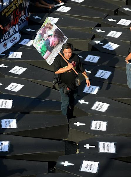 A Philippine journalist walks among mock coffins during a protest at the Malacanang Palace in Manila, on November 23, 2012, to commemorate the third anniversary of the November 23 Maguindanao massacre. The police said on Saturday they had shot dead a suspect in the 2009 killings of 58 people, the country's worst political massacre, after he hurled a grenade and fired a pistol at them