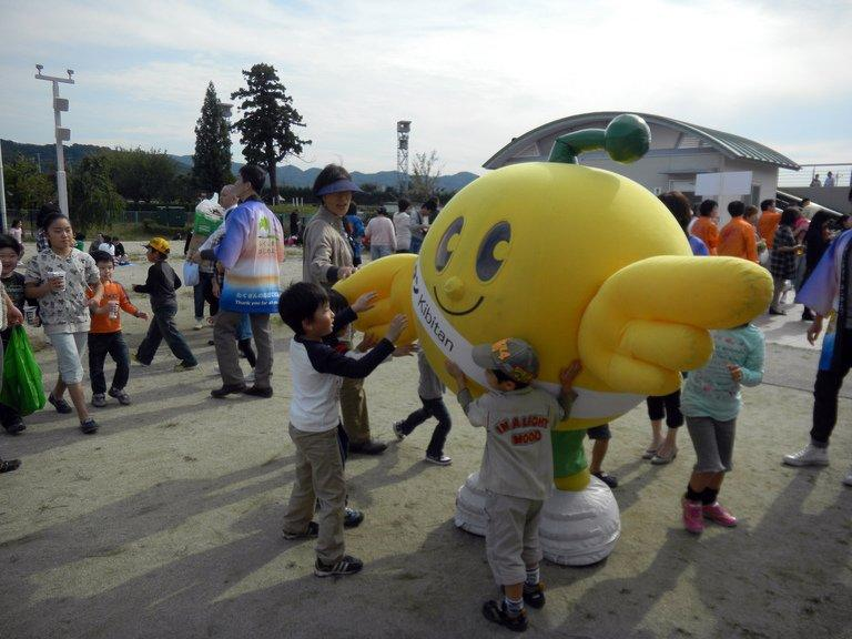 "Children play with a grinning bird mascot ""Kibitan"" in Fukushima on October 14, 2012"