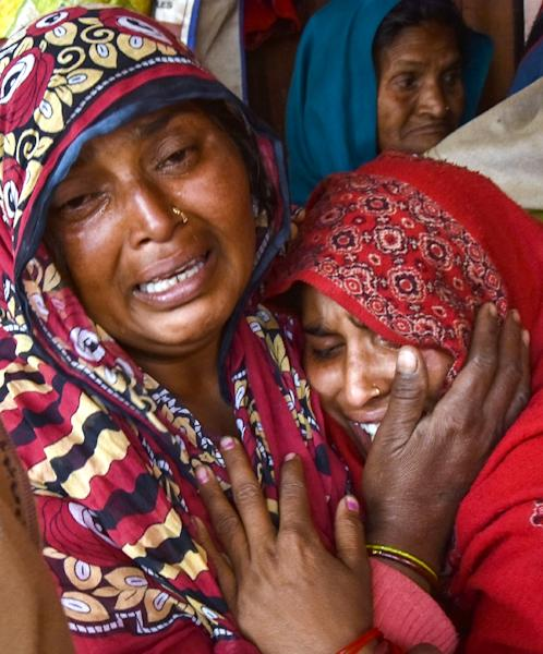 Indian relatives of victims who died from toxic locally-made alcohol cry at Saharanpur Civil Hospital in Saharanpur in the northern state of Uttar Pradesh (AFP Photo/)