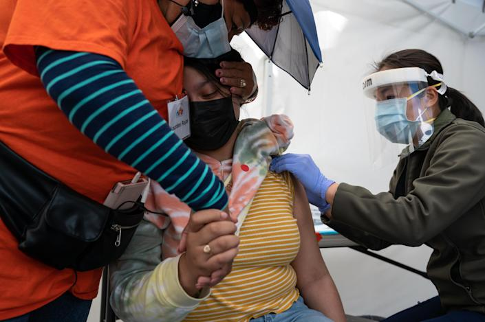 A woman receives a COVID-19 vaccination at the Unidos En Salud community vaccination and testing site in San Francisco on Aug. 1, 2021. (Mike Kai Chen/The New York Times)
