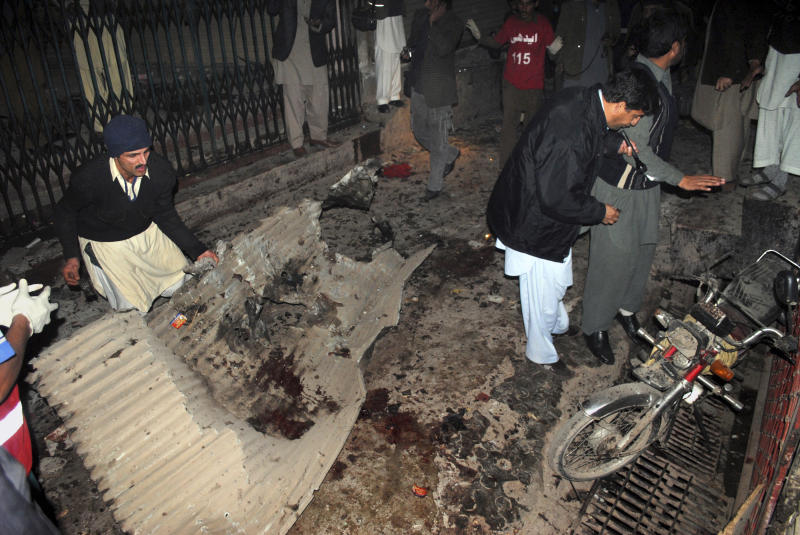 Pakistani plainclothes police officers and local residents examine at the site of a suicide bombing in Peshawar, Pakistan, Saturday, Dec. 22, 2012. A suicide bomber in Pakistan killed several people including a provincial government official at a political rally held Saturday by a party that has opposed the Taliban, officials said. (AP Photo/Sohail Iqbal)