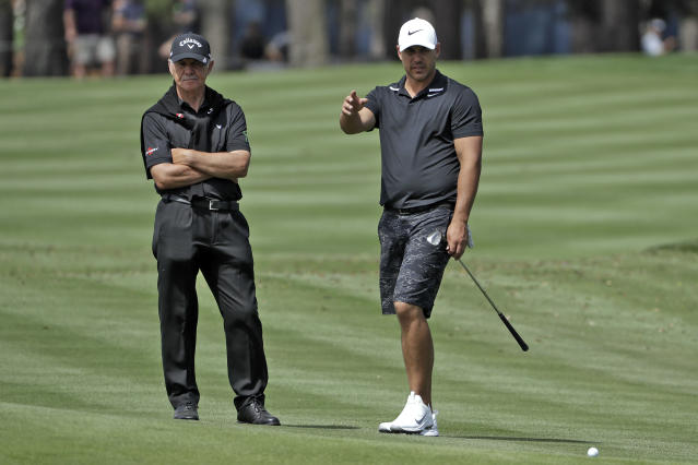 Brooks Koepka, right, gestures as he talks to his short game coach Peter Cowen during a practice round for The Players Championship golf tournament Wednesday, March 11, 2020, in Ponte Vedra Beach, Fla. (AP Photo/Chris O'Meara)