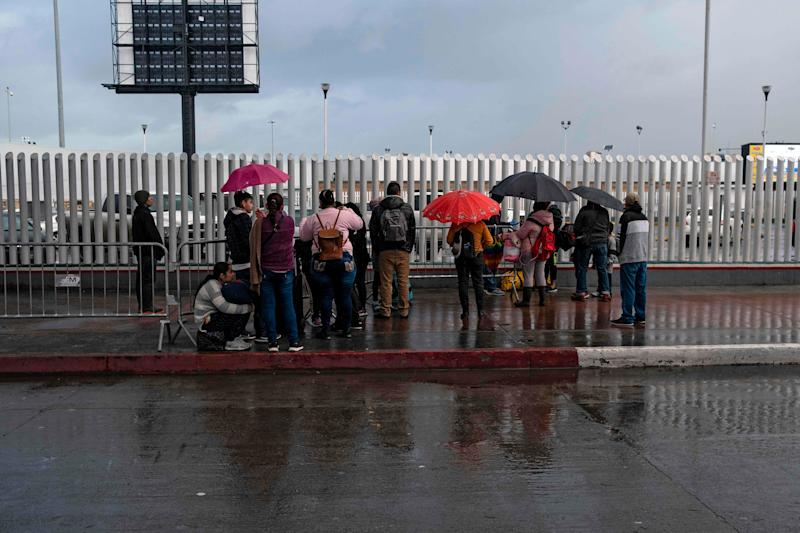 Asylum seekers wait for news outside El Chaparral port of entry on the U.S.-Mexico border in Tijuana, Mexico, on March 19, 2020.