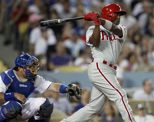 Philadelphia Phillies' Jimmy Rollins, right, hits an RBI single with Los Angeles Dodgers catcher A.J. Ellis, left, looking on in the fifth inning during a baseball game Thursday, June 27, 2013, in Los Angeles. (AP Photo/Alex Gallardo)