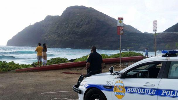 PHOTO: Police wait for people to return to their cars before closing the beach parking lot in preparation for Hurricane Douglas, in Honolulu, on July 26, 2020. (Ronen Zilberman/AFP via Getty Images, FILE)