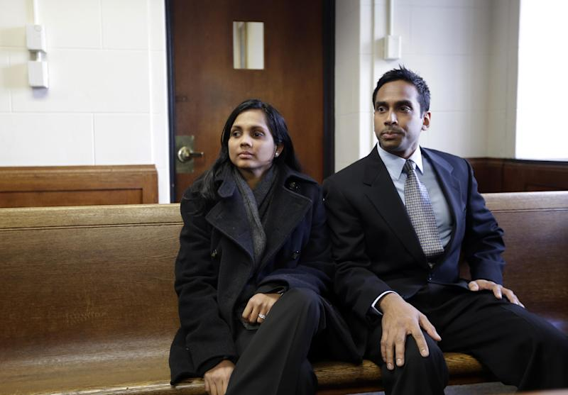Annie Dookhan, left, sits with an unidentified man, right, in Suffolk Superior Court moments before her arraignment in Boston, Thursday, Dec. 20, 2012. Dookhan, the former chemist at the center of a U.S. drug testing scandal, pleaded not guilty to charges including perjury and tampering with evidence. (AP Photo/Steven Senne, Pool)