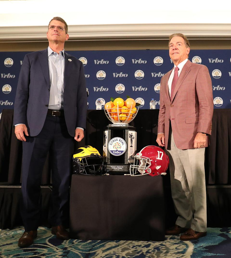 Michigan head coach Jim Harbaugh and Alabama head coach Nick Saban pose with the Citrus Bowl trophy Tuesday, December 31, 2019 at the Rosen Plaza Hotel in Orlando, Fl.