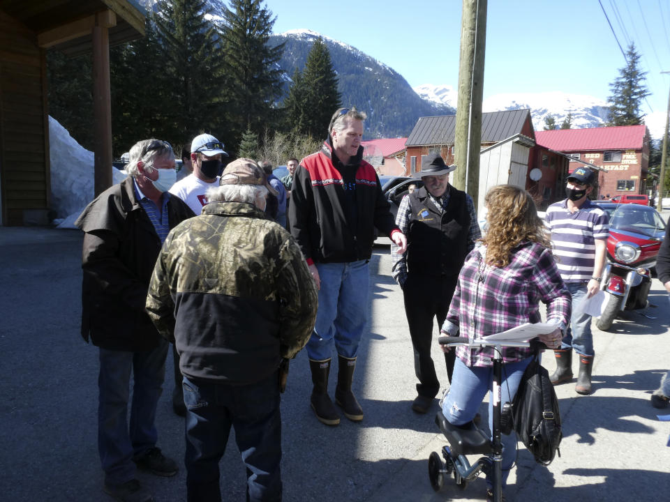 Alaska Gov. Mike Dunleavy, center, meets with people near an outdoor COVID-19 vaccination clinic in Hyder, Alaska, on Thursday, April 22, 2021. Dunleavy said Alaska is in a fortunate position with its vaccine supply and he wants to share vaccines with people across the border in Stewart, British Columbia, a community that has close ties to Hyder. (AP Photo/Becky Bohrer)