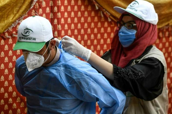 A health official helps another one to arrange protective gear before taking a test sample from patients at a drive-through screening and testing facility for the COVID-19 coronavirus in Islamabad in June 2020 (AFP Photo/Aamir QURESHI)