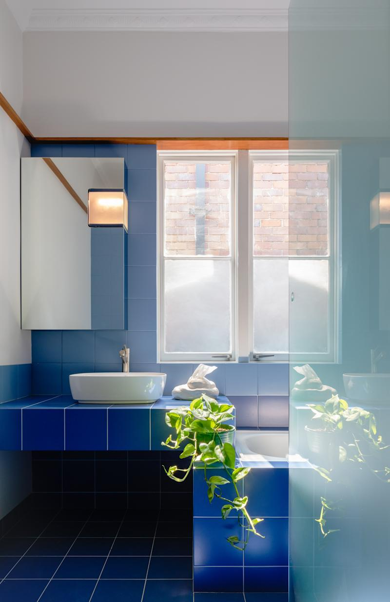 Qianyi converted a second bedroom into a bathroom and laundry, using the same blue shade as in the kitchen. She likes how the blue tiles also mimic the shape of the glass blocks.