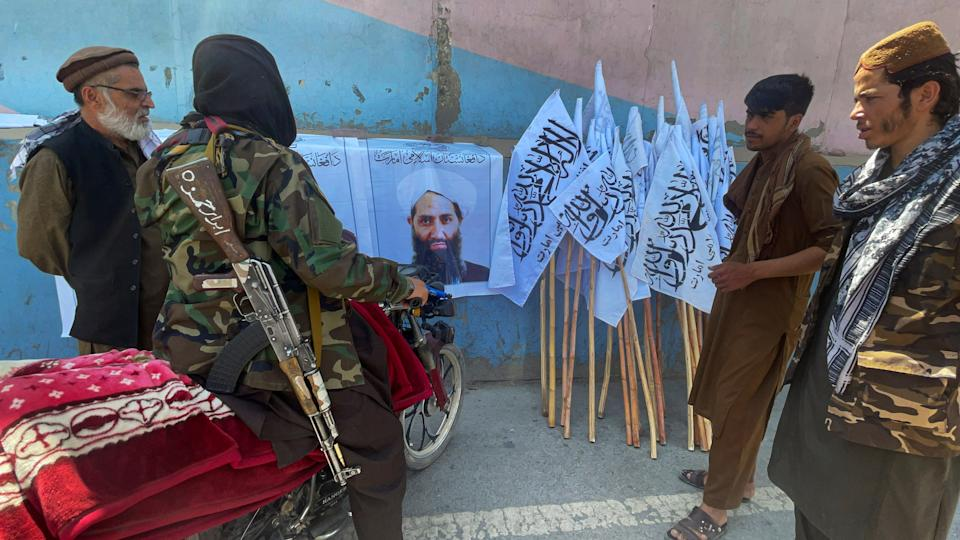 Members of Taliban forces gather and look at the picture of their leader Mullah Haibatullah Akhundzada, in Kabul. (Reuters)