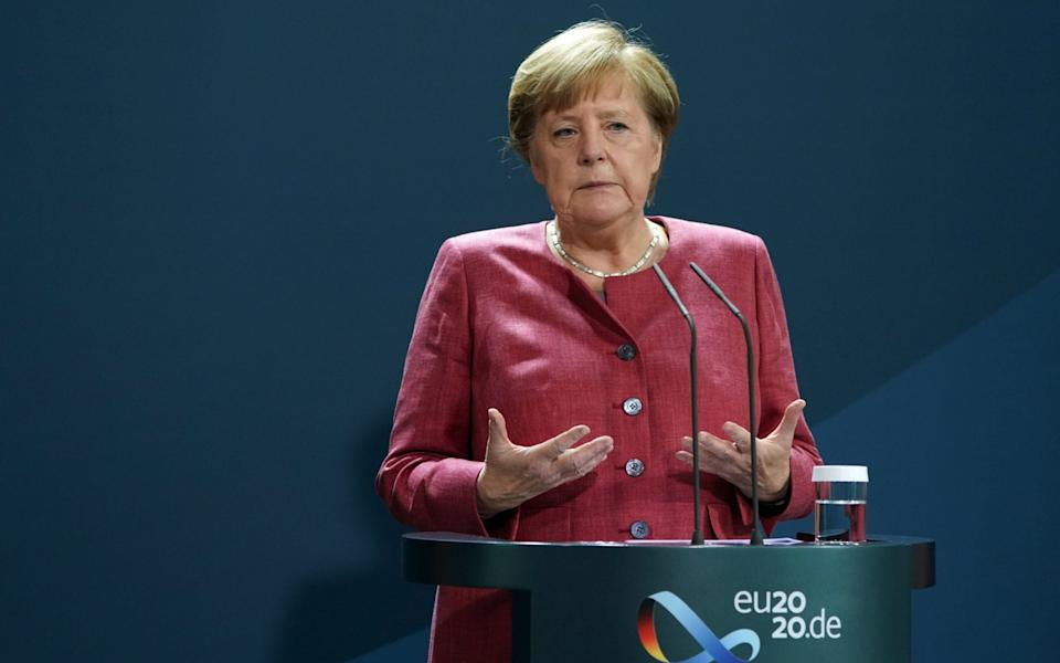 Angela Merkel speaking after 16 German cities and counties exceeded the warning value of 50 new Covid-19 infections per 100,000 inhabitants in seven days - Shutterstock