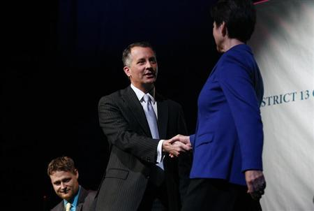 Democrat Alex Sink and Republican David Jolly, both candidates for Florida's congressional District 13, shake hands before participating in a candidate forum which included Libertarian Lucas Overby in Clearwater