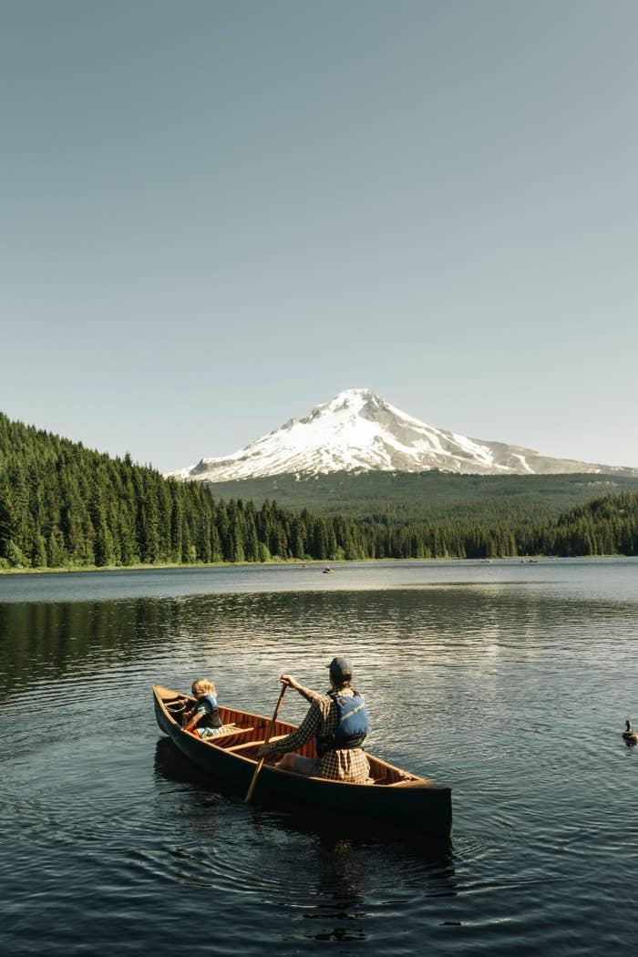 A dad and a daughter canoeing in a lake